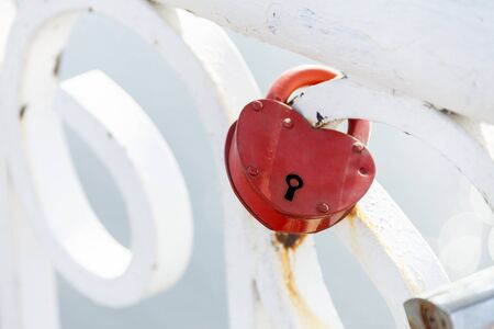 Red heart-shaped lock denoting love hanging on a white fence Foto de archivo