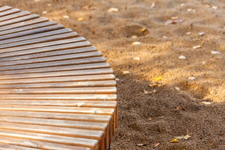 Abstract background texture. Fragment of a wooden semicircular bench on a background of sand with autumn leaves