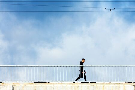 A man walks on a bridge against the sky. Flat view in profile.