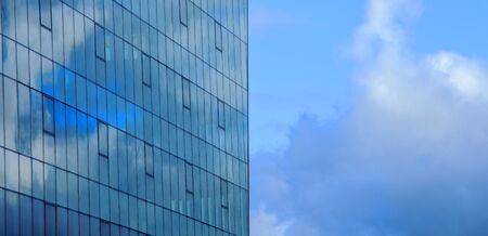 Fragment of the facade of a glass building against the sky with reflection of clouds