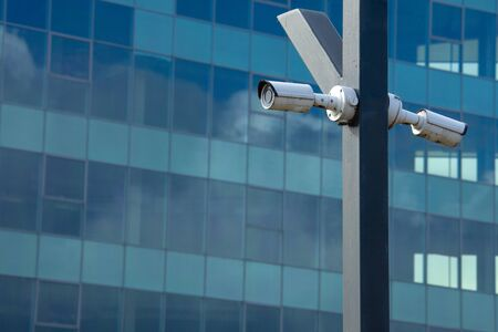 Two surveillance cameras mounted on a pillar against the background of a glass business center Foto de archivo