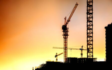 Silhouettes of residential buildings and construction cranes against the sunset sky.