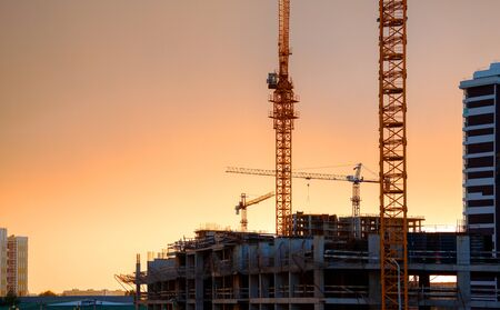 View of the building process. Construction site with cranes and monolithic buildings against the sunset sky