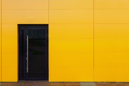 The bright facade of the building is sheathed in aluminum with one glass door