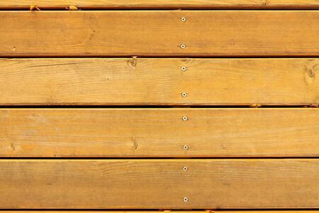 Board flooring with crevices, nails, self-tapping screws, and yellow autumn leaves