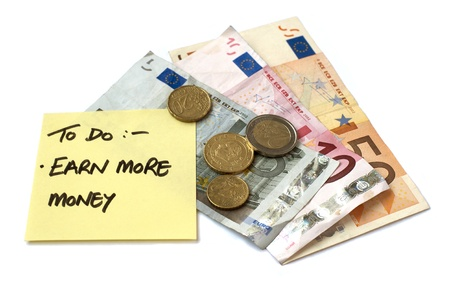 earn more: To Do List Earn More Money post it note stuck to pile of savings money both bank notes and loose change in Euro currency Stock Photo