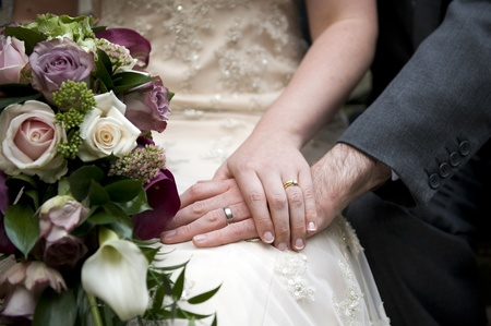 Detail shot of wedding couple holding hands featuring the rings and bridal bouquet of muted roses and kala lillies photo