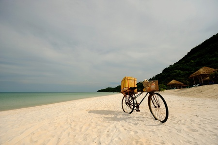 Old pedal bike with woven baskets stuck in sand on beautiful white sand beach photo