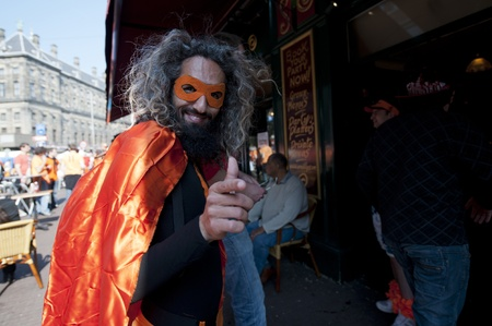 dam square: Bearded man with crazy gray hair in bright orange fancy dress celebrating Dutch national holiday Queens Day in April 2011 in Dam Square Editorial