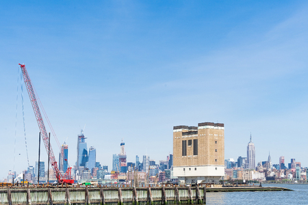 Floating construction crane on Hudson River, Jersey City in the background, USA