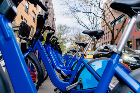 Row of city bikes for rent at docking stations in New York, USA Stock Photo