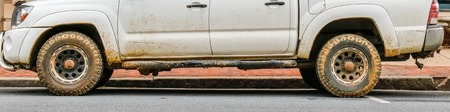 Half view of dirty pickup truck after rain Foto de archivo