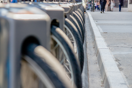 Close-up of bike tire parked in bikes docking station. Row of bikes for rent at docking stations in New York, USA