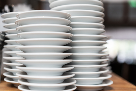 Close-up view of pile of white plates in restaurant 스톡 콘텐츠