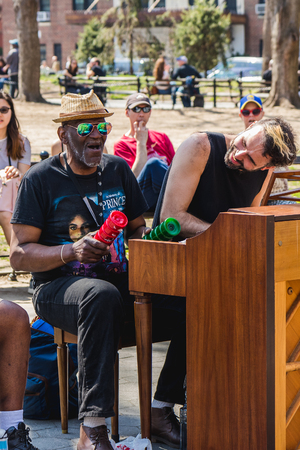 NEW YORK, USA - APRIL 14, 2018: Men singing and playing the piano in the park near with West Village, New York City, USA Editorial