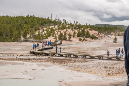 YELLOWSTONE NATIONAL PARK, WYOMING, USA - JUNE 19, 2018: Tourists at Yellowstone National Park. The boardwalk among pools and geysers. The barren snow-colored basin. Porcelain Basin of Norris Geyser Basin, Yellowstone National Park