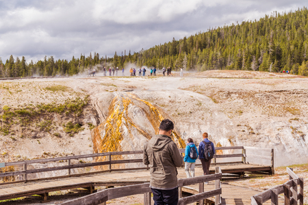YELLOWSTONE NATIONAL PARK, WYOMING, USA - JUNE 18, 2018: Tourists at Yellowstone National Park. The boardwalk among pools and geysers. The barren snow-colored basin. Porcelain Basin of Norris Geyser Basin, Yellowstone National Park