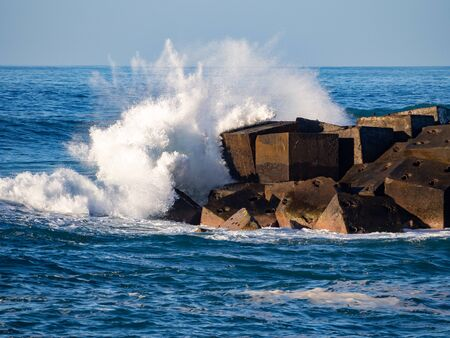 Waves breaking on concrete blocks in Pueto de la Cruz, Tenerife