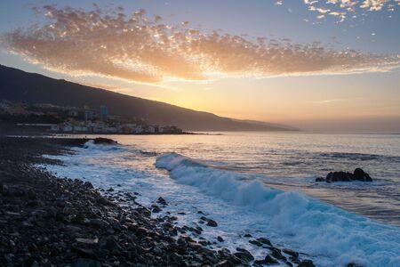 Black pebble beach in Puerto de la Cruz by the sunset , Tenerife, Canary Islands Spain
