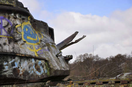 destroyed tank with graffiti and broken cannon Stock Photo