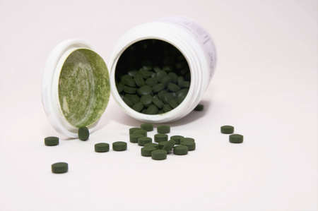 dose of green pills isolated on whte background Stock Photo