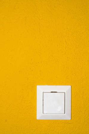 structured: Interruptor de luz blanca en una pared estructurada amarilla