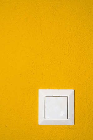 white light switch on a yellow structured wall