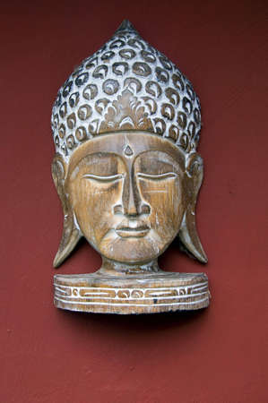 wooden buddha head in front of a red wall Stock Photo