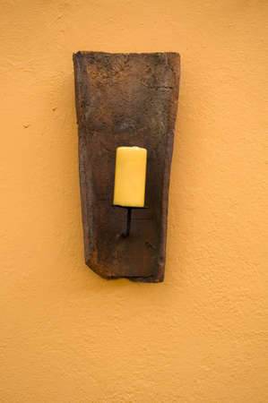 yellow candle in front of a yellow wall Stock Photo