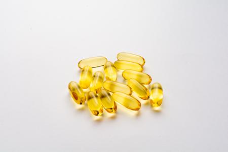 Golden fish oil capsule in white background