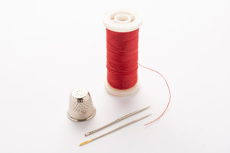 Red thread and a silver thimble and needles