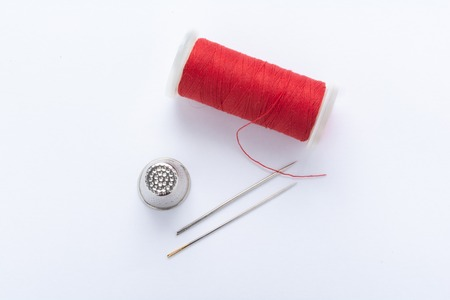 Flat lay of red thread, thimble and needles