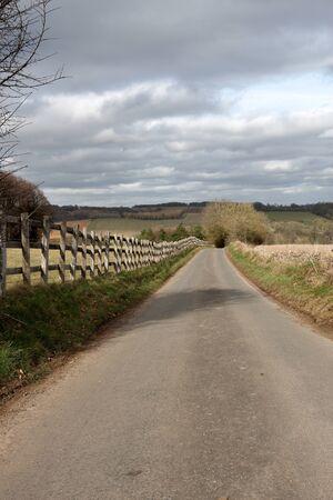 grass verge: Strada di campagna lungo interminabili con una staccionata in legno e un cielo tempestoso