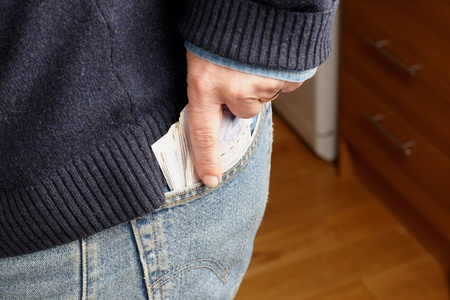 putting money in pocket: A man putting money in his jeans pocket