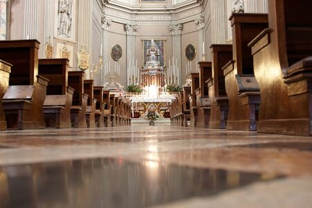 pews: The aisle of a grand church leading towards the altar