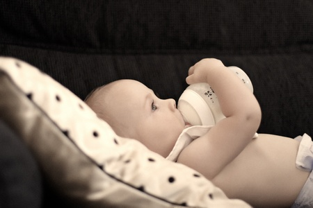 baby feeding: A six month old baby drinking milk while holding his bottle himself  Stock Photo
