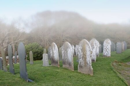 head stones: A cemetery old head stones and fog Stock Photo