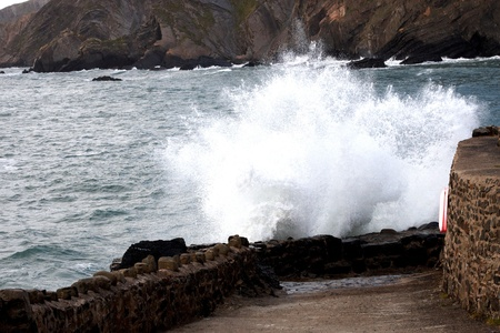 slipway: Rough sea splashing against the wall on a slipway