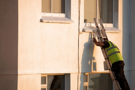A man up a ladder painting the exterior of a house Stock Photo - 11712603