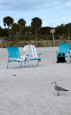toweling: Three empty deck chairs on a sandy beach
