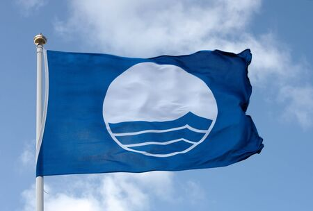 wavering: A clean beach flag wavering against blue sky