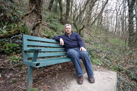 Mature man sitting on a park bench photo