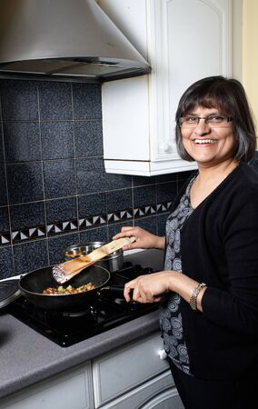 An indian lady in the kitchen making a curry photo