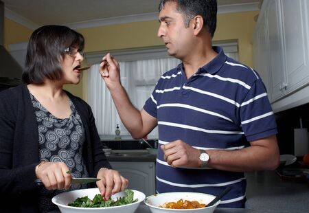 An Asian woman being spoon fed  by her husband photo