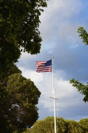 wavering: The American Flag wavering against a blue sky