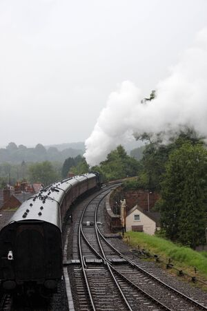 A steam train traveling on the tracks with steam rising in the air Stock Photo - 14600952