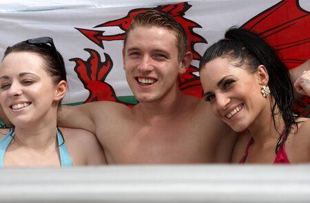 welsh flag: Due femmine e un maschio con la bandiera gallese in un bagno caldo