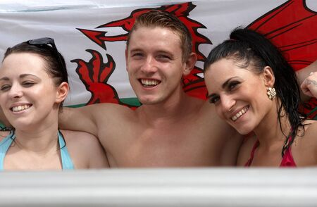welsh flag: Two females and one male with the Welsh flag in a hot bath