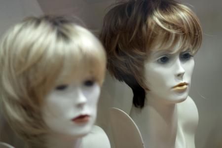 wigs: Wigs on display on manikin heads in a shop Stock Photo