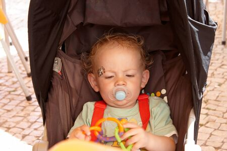 soother: Toddler sitting in his pushchair playing with his toy
